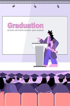 Vrouwelijke afgestudeerde student geeft toespraak van tribune afgestudeerden vieren academisch diploma diploma onderwijs universiteit certificaat concept verticaal volledige lengte certificate