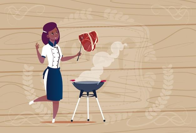 Vrouwelijke afrikaanse amerikaanse chef-kok die de leider van het vleesbeeldverhaal in restaurant eenvormig over houten geweven achtergrond roosteren