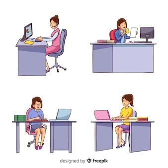 Vrouwelijke arbeiders die bij geplaatste bureaus zitten