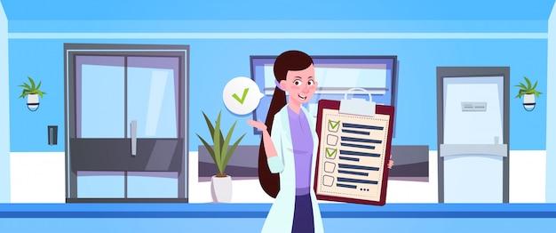 Vrouwelijke arts hold klembord over ziekenhuiswachtkamer