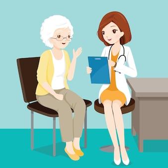 Vrouwelijke arts in gesprek met oudere patiënt over haar symptomen