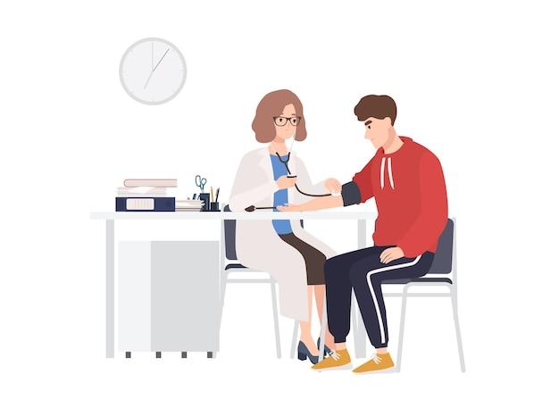 Vrouwelijke arts of medisch adviseur zit aan bureau en meet de bloeddruk van mannelijke patiënt.