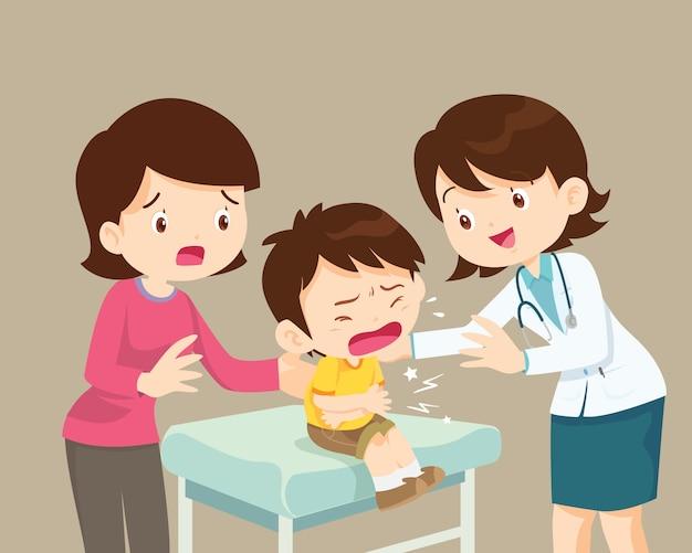 Vrouwelijke arts troost haar huilende patiënt jongen met moeder