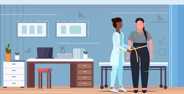 Vrouwelijke arts voedingsdeskundige meten vrouw taille lichaam medisch overleg zwaarlijvigheid gewichtsverlies concept moderne kliniek kantoor interieur volledige lengte horizontaal