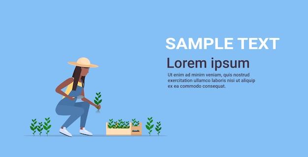 Vrouwelijke boer aanplant landbouw zaailingen vrouw landbouwarbeider tuinieren eco landbouwconcept volledige lengte horizontaal