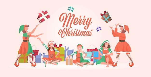 Vrouwelijke elfen team gooien geschenk huidige dozen vrolijk kerstfeest gelukkig nieuwjaar winter vakantie viering concept groet