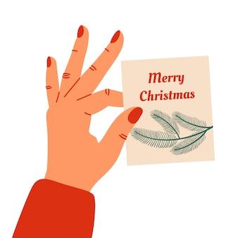 Vrouwelijke hand houdt speels een wenskaart voor merry christmas. vector illustratie