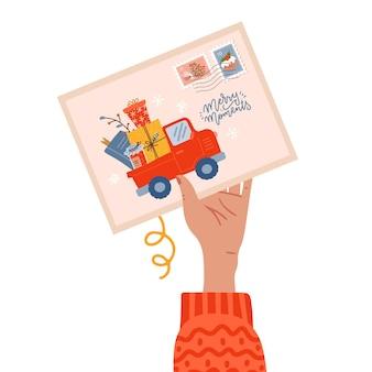 Vrouwelijke hand met ansichtkaart met kerststempel en vrolijke momenten belettering tekst met pick-up truck...