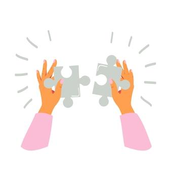Vrouwelijke handen houdt stukjes puzzel vast en vouwt deze
