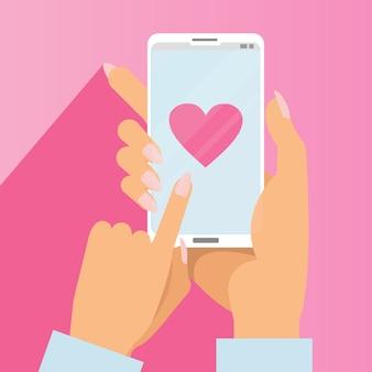 Vrouwelijke handen met telefoon met groot hart op scherm.