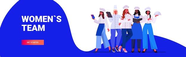 Vrouwelijke koks in uniform staan samen mooie vrouwen chef-koks koken voedingsindustrie concept professionele restaurant keuken werknemers volledige lengte horizontale vector illustratie