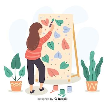 Vrouwelijke kunstenaar die een canvas met bloemenmotief schildert