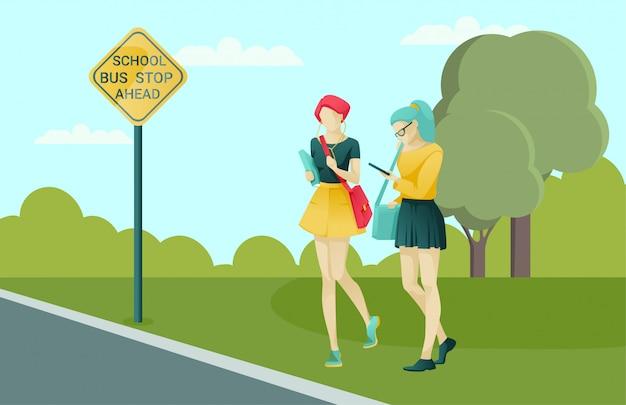 Vrouwelijke leerlingen wachten vervoer op school bushalte