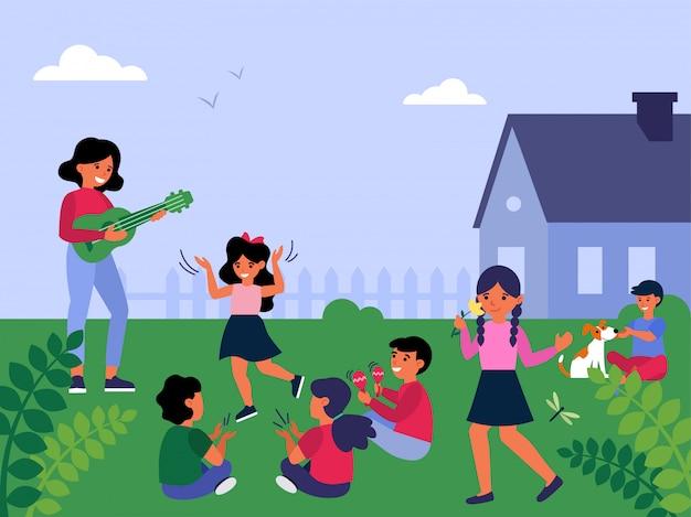 Vrouwelijke leraar gitaar spelen aan kinderen buiten spelen