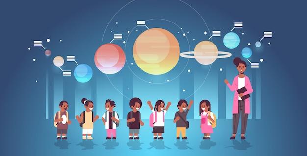 Vrouwelijke leraar met afro-amerikaanse schoolkinderen in observatorium zonnestelsel verkenning schoolreisje excursie naar planetarium astronomie lesconcept plat volledige lengte horizontaal