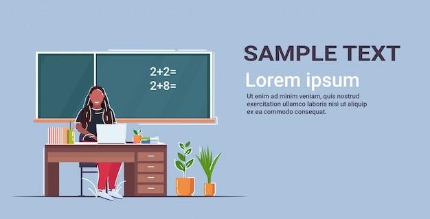 Vrouwelijke leraar zit aan bureau voor schoolbord afro-amerikaanse vrouw met laptop op wiskunde les basisschool onderwijs concept klas interieur horizontale kopie ruimte