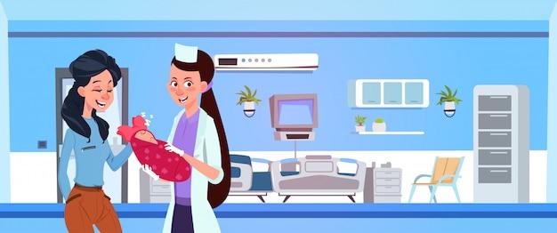 Vrouwelijke medische arts geven pasgeboren aan gelukkige moeder in ziekenhuis ward