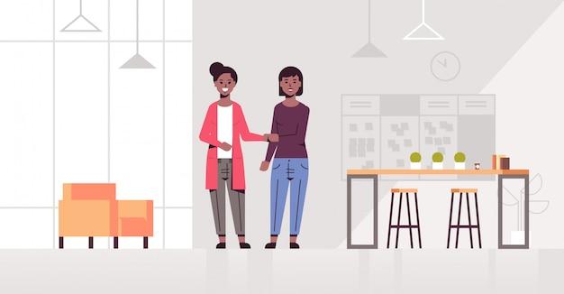Vrouwelijke ondernemers handshaking zakelijke partners handbewegingen tijdens vergadering overeenkomst partnerschap concept creatief co-working center modern kantoor interieur volledige lengte horizontaal