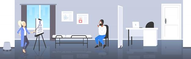 Vrouwelijke oogarts oog visie van afro-amerikaanse man patiënt zicht arts wijzende brieven op grafiek geneeskunde gezondheidszorg concept moderne kliniek kamer interieur volledige lengte horizontaal