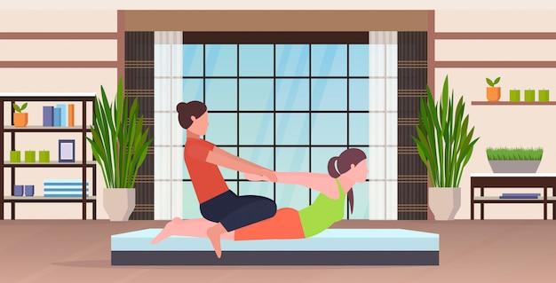 Vrouwelijke persoonlijke trainer die rekoefeningen doen met de instructeur die van de meisjesgeschiktheid vrouw helpen om het concept van de spierentraining uit te rekken moderne van de de yogagymnastiek van de yogastudio binnenlandse vlakke volledige volledige lengte horizontaal