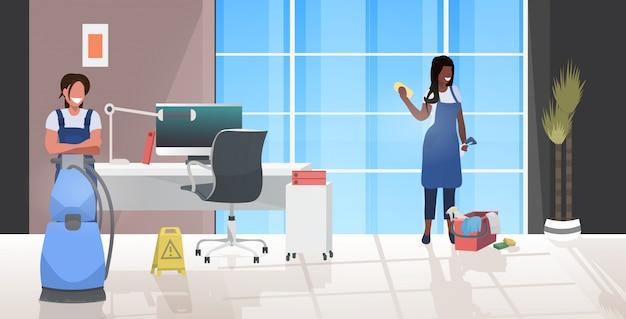 Vrouwelijke schoonmakers met behulp van stofzuiger en vod mix race conciërges team in uniform samen te werken schoonmaak concept moderne kantoor interieur horizontale volledige lengte vectorillustratie