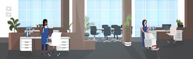 Vrouwelijke schoonmakers met behulp van stofzuiger en vod mix race conciërges team in uniform samen te werken schoonmaak concept moderne kantoor interieur horizontale volledige lengte