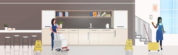 Vrouwelijke schoonmakers met stofzuiger doek en voorzichtigheid nat vloer teken mix race conciërges team in uniform samen te werken schoonmaak concept moderne kantoor keuken interieur
