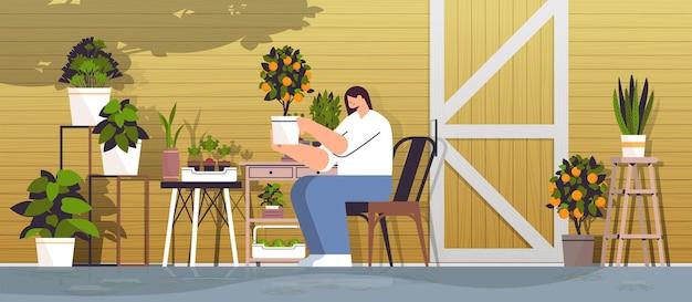 Vrouwelijke tuinman die voor een oranje potplant zorgt in de achtertuin of de moestuin horizontaal
