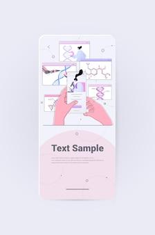 Vrouwelijke wetenschapper die microscoop gebruikt die de dna-structuur analyseert op het scherm van de smartphone, onderzoeker die experiment maakt in het laboratorium dna-testen van genetisch manipulatieconcept