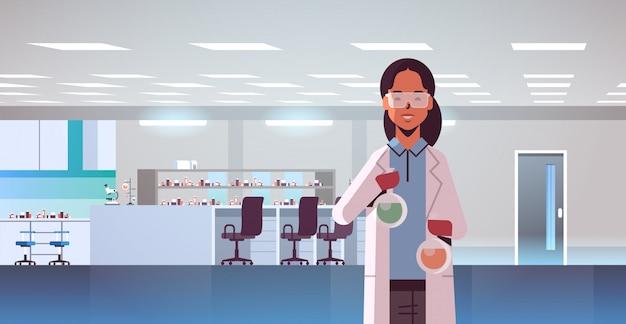 Vrouwelijke wetenschapper die reageerbuizen met kleurrijke vloeistof houdt