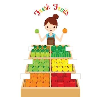 Vrouwelijke winkelier met veel fruit in lade, gezond eten