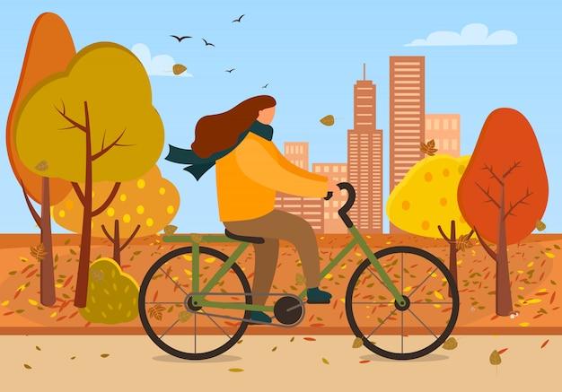 Vrouwen berijdende fiets in autumn park of city