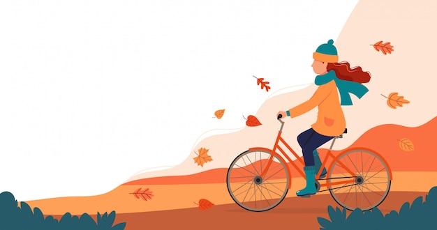 Vrouwen berijdende fiets in de herfst.
