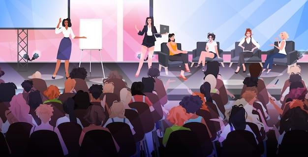 Vrouwen die een presentatie maken en voor het publiek spreken vanaf het podium. vrouwenclubmeisjes die elkaar ondersteunen, unie van feministisch concept