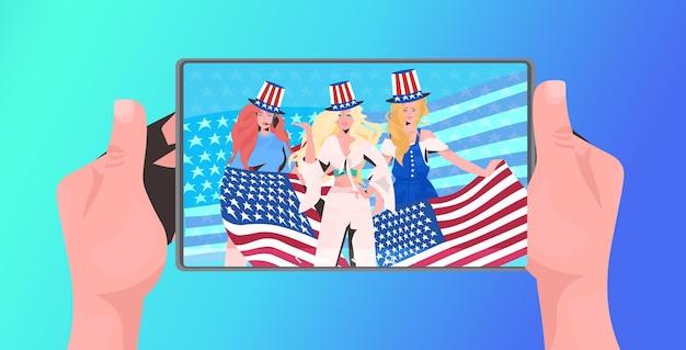 Vrouwen in feestelijke hoed met usa vlaggen vieren 4 juli amerikaanse onafhankelijkheidsdag viering smartphone scherm portret vectorillustratie
