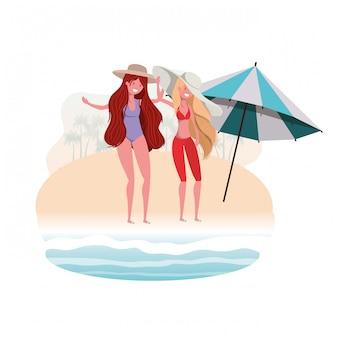 Vrouwen met zwempak op het strand en paraplu