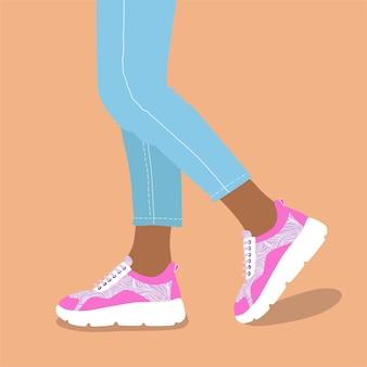 Vrouwenbenen in trendy sneakers met witte en roze kleuren.