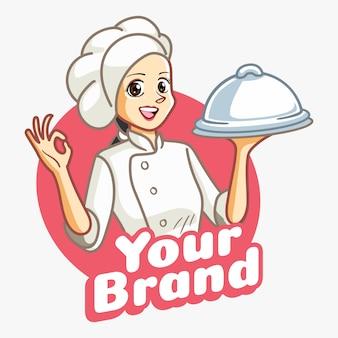 Vrouwenchef-kok met witte kleren en dien voedselhulpmiddel op haar hand.
