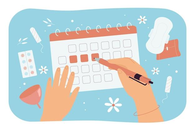 Vrouwenhanden die menstruatiedagen op kalender markeren