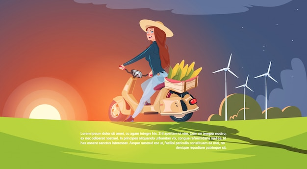 Vrouwenlandbouwer die elektrische autoped met oogst in doos in platteland over mooie zonsondergang backgr berijden