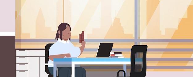 Vrouwenmanager gebruikend laptop en etend van de de zittingswerkplaats van het chocolademeisje het moderne horizontale portret van het het levensstijl binnenlandse ongezonde levensstijlconcept