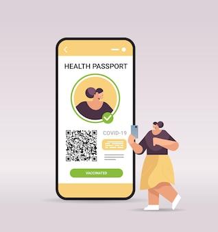 Vrouwenreiziger die digitaal immuniteitspaspoort gebruikt met qr-code op smartphonescherm, risicovrij covid-19 pandemie