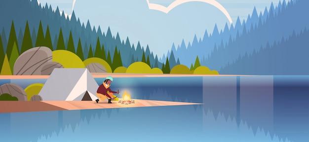 Vrouwenwandelaar die brand dichtbij tentkamp maken die het brandhout van de meisjesholding voor vuur het kamperen van de het landschapsaard van de landschapsaard van de rivierbos bergen horizontale volledige lengte als achtergrond wandelen