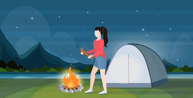 Vrouwenwandelaar die het brandhout van de brandmeisje voor vuur maken die kamperende conceptenreiziger wandelen op het landschaps van de stijgings mooie nacht horizontale volledige lengte als achtergrond