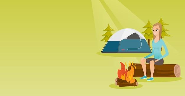 Vrouwenzitting op logboek dichtbij kampvuur in het kamperen.