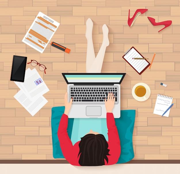 Vrouwenzitting op vloer met laptop