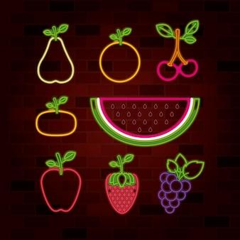 Vruchten die in neonteken op bakstenen muur worden geplaatst