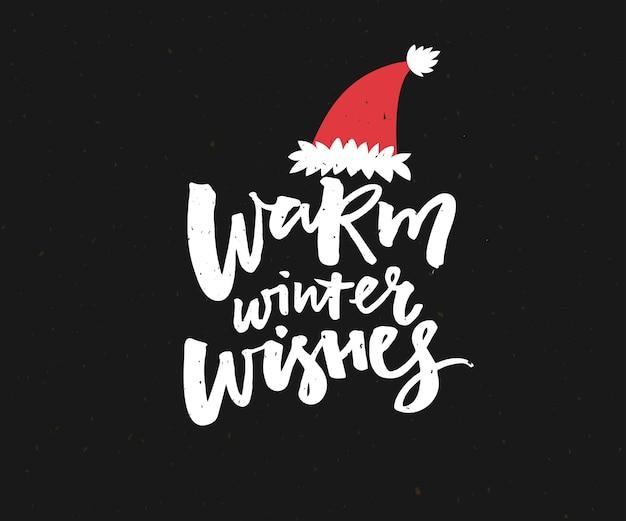 Warme winterwensen. kerstkaartontwerp met borstelbelettering in rode kerstmuts.