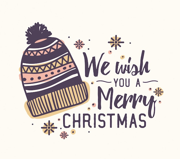 We wish you a merry christmas-letters geschreven met een elegant lettertype en versierd met een gebreide wollen muts en sneeuwvlokken