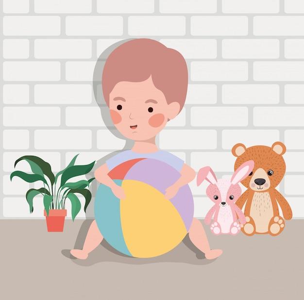 Weinig babyjongen met ballonplastiek en gevuld speelgoed